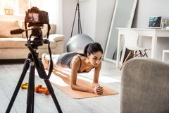 Sporty young trainer demonstrating home exercises on camera royalty free stock photo