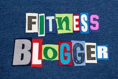 FITNESS BLOGGER text word collage colorful fabric on blue denim, health and fitness blogs and blogging. Horizontal aspect royalty free stock photo