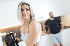 Fitness woman in kitchen, man in background. Husband and wife cooking together. Fitness blond women in kitchen, men in black T-shirt in background. Husband and royalty free stock photography