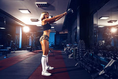 Fitness blonde girl posing and exercising with dumbbell. In gym royalty free stock images
