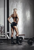 Fitness blonde girl prepares for exercising with barbell in gym Stock Image