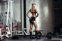 Fitness blonde girl prepares for exercising with barbell in gym Stock Images