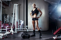 Fitness blonde girl prepares for exercising with dumbbell in gym Stock Photo