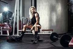 Fitness blonde sexy woman posing on bench in the gym. Fitness blonde sexy girl posing on bench in the gym in military style clothes Royalty Free Stock Photo