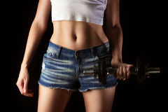 Fitness body. In jeans on the black background Stock Photo