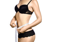Fitness body with a measurement tape. Beautiful athletic slim woman measuring her waist by measure tape. Stock Images