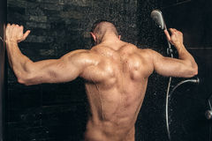 Fitness bodybuilder taking a shower after training. Close up details of back muscles in shower Stock Photos