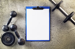 Fitness or bodybuilding background. Old iron dumbbells on conrete floor in the gym. Photograph taken from above, top. Fitness or bodybuilding concept background royalty free stock images