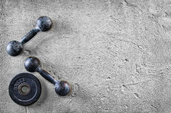 Fitness or bodybuilding background. Old iron dumbbells on conrete floor in the gym. Photograph taken from above, top. Fitness or bodybuilding concept background stock photos