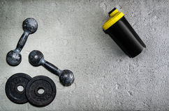 Fitness or bodybuilding background. Old iron dumbbells on conrete floor in the gym. Photograph taken from above, top Stock Photography