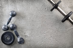 Fitness or bodybuilding background. Old iron dumbbells on conrete floor in the gym. Photograph taken from above, top. Fitness or bodybuilding concept background royalty free stock photography