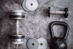Fitness or bodybuilding concept background. Old iron dumbbells and Kettlebell on grey, conrete floor in the gym. royalty free stock photo