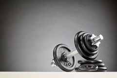 Fitness or Bodybuilding Equipment. Bodybuilding or fitness equipment - a dumbbell resting on a stack of black weight discs Stock Photos