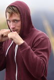Fitness boxer boxing outside on road in hoodie Stock Image