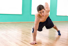 Fitness boy in sport club. Photo of handsome young sporty man. Sportsman doing plank in sport club and looking at camera Royalty Free Stock Images
