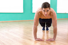 Fitness boy in sport club. Photo of handsome young sporty man. Sportsman doing plank and push ups in sport club and looking at camera Royalty Free Stock Image
