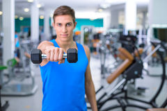 Fitness boy in sport club. Photo of handsome young sporty man. Sportsman training with dumbbell in sport club with exercise equipments. Man stretching and Stock Photos