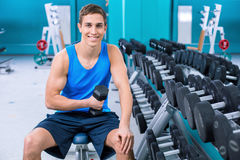 Fitness boy in sport club. Photo of handsome young sporty man. Sportsman training with dumbbell in sport club. Man smiling and looking at camera Royalty Free Stock Photo