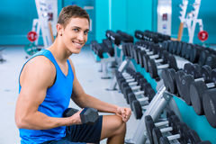 Fitness boy in sport club. Photo of handsome young sporty man. Sportsman training with dumbbell in sport club. Man smiling and looking at camera Stock Image