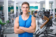 Fitness boy in sport club. Photo of handsome young sporty man. Sportsman training in sport club with exercise equipments. Man smiling and looking at camera Stock Photo