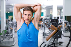 Fitness boy in sport club. Photo of handsome young sporty man. Sportsman training in sport club with exercise equipments. Man stretching and looking at camera Royalty Free Stock Image