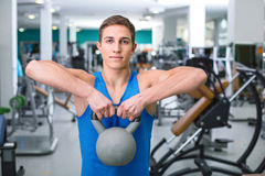 Fitness boy in sport club. Photo of handsome young sporty man. Sportsman training with weight in sport club with exercise equipments. Man stretching and looking Royalty Free Stock Photo