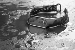 Fitness bracelet on a black slate background with drops of water stock image