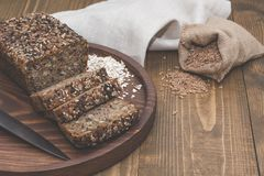 Fitness bread. A loaf of fresh rustic whole meal rye bread, sliced on a wooden board, rural food background. Top view. Copy space. Stock Photos
