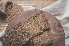 Fitness bread. A loaf of fresh rustic whole meal rye bread, sliced on a wooden board, rural food background. Top view. Stock Images