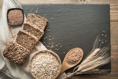 Fitness bread. A loaf of fresh rustic whole rye bread with wheat, sliced on a black slate dish and board, rural food background. T. Fitness wholegrain bread. A Royalty Free Stock Photo