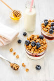 Fitness breakfast with granola, milk and honey on white background Stock Photos