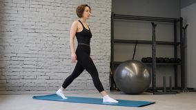 Fitness Caucasian woman doing lunges exercises for leg muscles workout training in gym. Active girl doing front forward one leg st. Ep lunge exercise side view stock footage