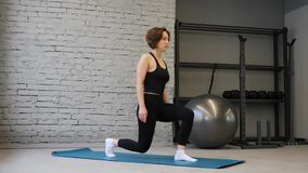 Fitness Caucasian woman doing lunges exercises for leg muscles workout training in gym. Active girl doing front forward one leg st