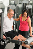 Fitness center active man exercising with trainer. Fitness center active men exercising legs with personal trainer Stock Photography