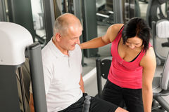 Fitness center active man exercising with trainer Stock Images
