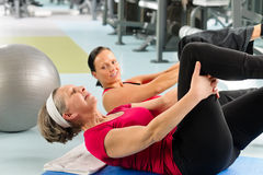 Fitness center senior woman exercise gym workout. Fitness center senior women exercise sit ups with personal trainer Stock Photos