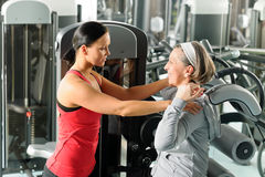 Fitness center senior woman exercise with trainer. Fitness center senior women exercise with personal trainer on machine Royalty Free Stock Images