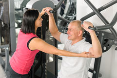 Fitness center trainer assist man exercise back. Fitness center personal trainer assist men exercise shoulder on machine Royalty Free Stock Images
