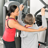 Fitness center trainer senior woman exercise. Fitness center personal trainer senior women exercise shoulder on machine Stock Photography
