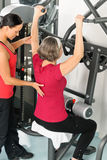 Fitness center trainer senior woman exercise. Fitness center personal trainer senior women exercise shoulder on machine Stock Image