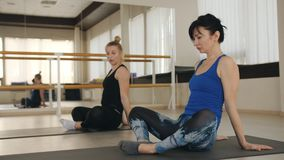Fitness center. two women doing sports Pilates exercises in the gym. Two girls works with a coach in a fitness gym. Two women in the gym do aerobics. Pilates stock video