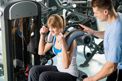 Fitness center young woman exercise with trainer Stock Image
