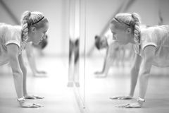 Fitness challenge. Women doing push-ups in front of the mirror, monochrome Royalty Free Stock Photo