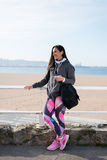 Fitness cheerful urban woman with smartphone Stock Images