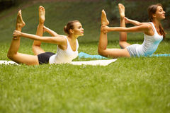 Fitness class. Beautiful young women doing exercise at summer pa Royalty Free Stock Photo