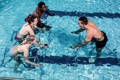 Fitness class doing aqua aerobics on exercise bikes. In swimming pool Royalty Free Stock Images