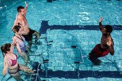 Fitness class doing aqua aerobics on exercise bikes. In swimming pool Stock Photo