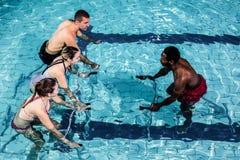 Fitness class doing aqua aerobics on exercise bikes. In swimming pool Royalty Free Stock Photo