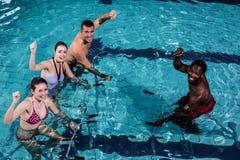 Fitness class doing aqua aerobics on exercise bikes. In swimming pool Stock Image