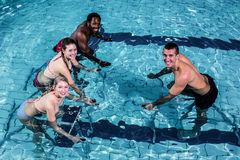 Fitness class doing aqua aerobics on exercise bikes. In swimming pool Royalty Free Stock Photos